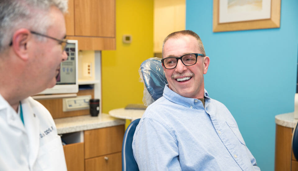 Dr. Bedich speaks with a smiling man who is sitting in a treatment chair in the dental office